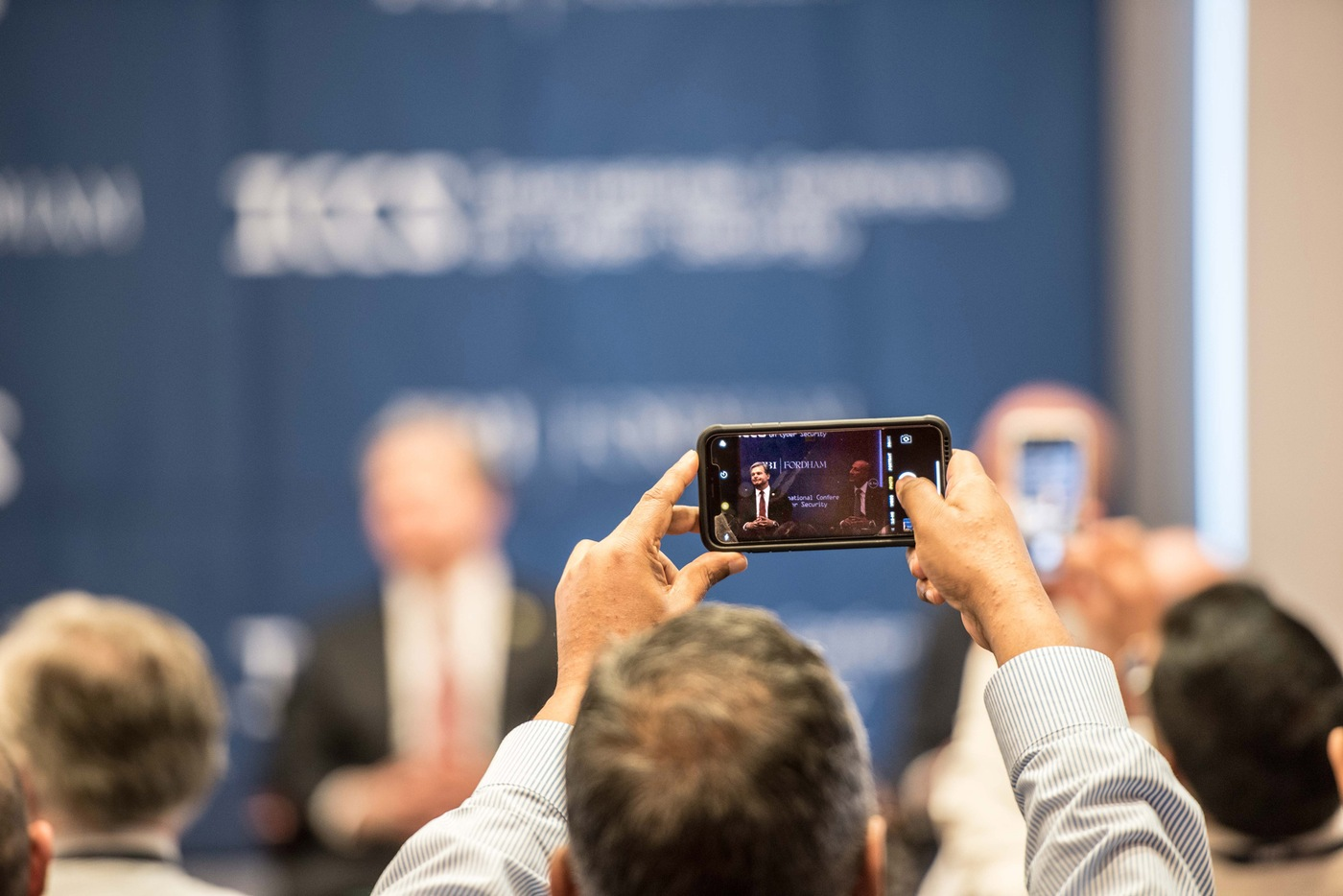 FBI Director Christopher Wray is seen through the phone of an audience member at the Fordham University/FBI-sponsored International Conference on Cyber Security in New York City on July 25, 2019.