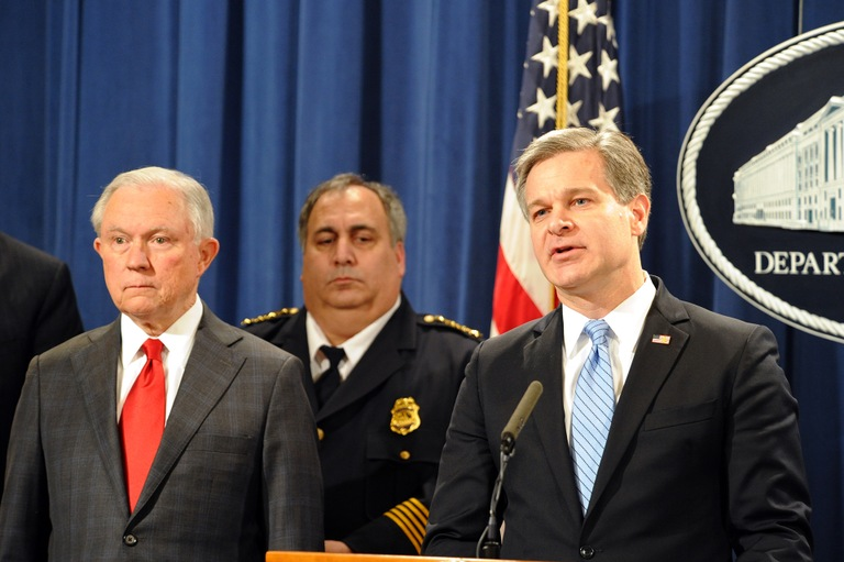 FBI Director Christopher Wray speaks at an October 26, 2018 press conference at the Department of Justice in Washington, D.C., regarding the arrest of Cesar Sayoc in connection with the mailing of multiple suspicious packages; Attorney General Sessions (left) and several other officials also spoke.