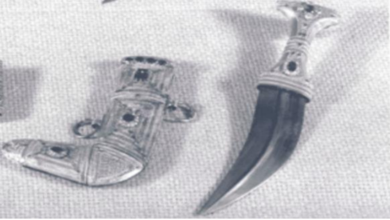 Weapon dagger hilt inlaid with 4 diamonds surrounding 1 emerald. Lower grip of dagger has 15 small diamonds surrounding oval ruby. Scabbard has 4 rubies at the throat and is also inlaid with an emerald over a ruby surrounded by 12 small diamonds. At tip of scabbard is ruby surrounded by 12 small diamonds.